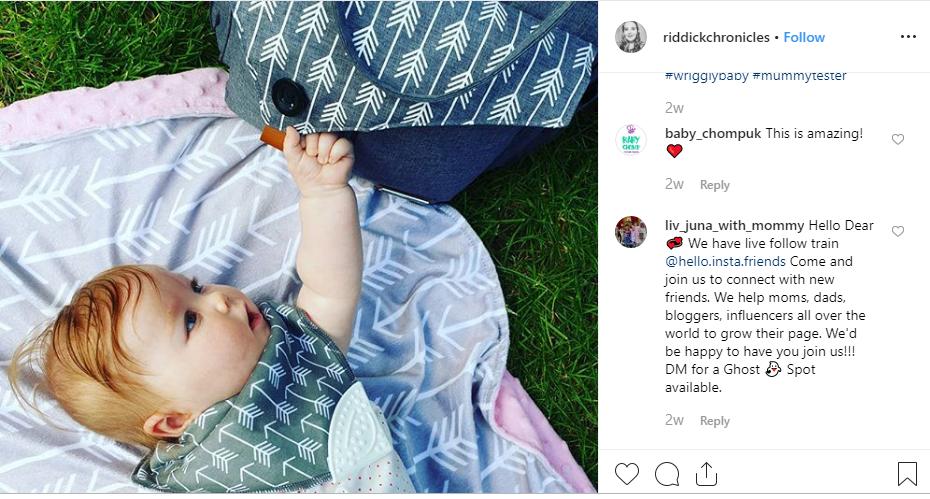 Baby mit einem Lekebaby Spucktuch, neben dem Lekebaby Wickelrucksack