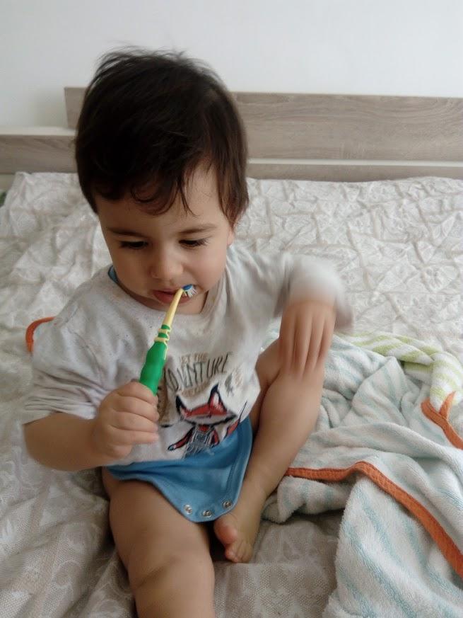baby spielt sitzend auf dem bett bevor gewickelt zu werden