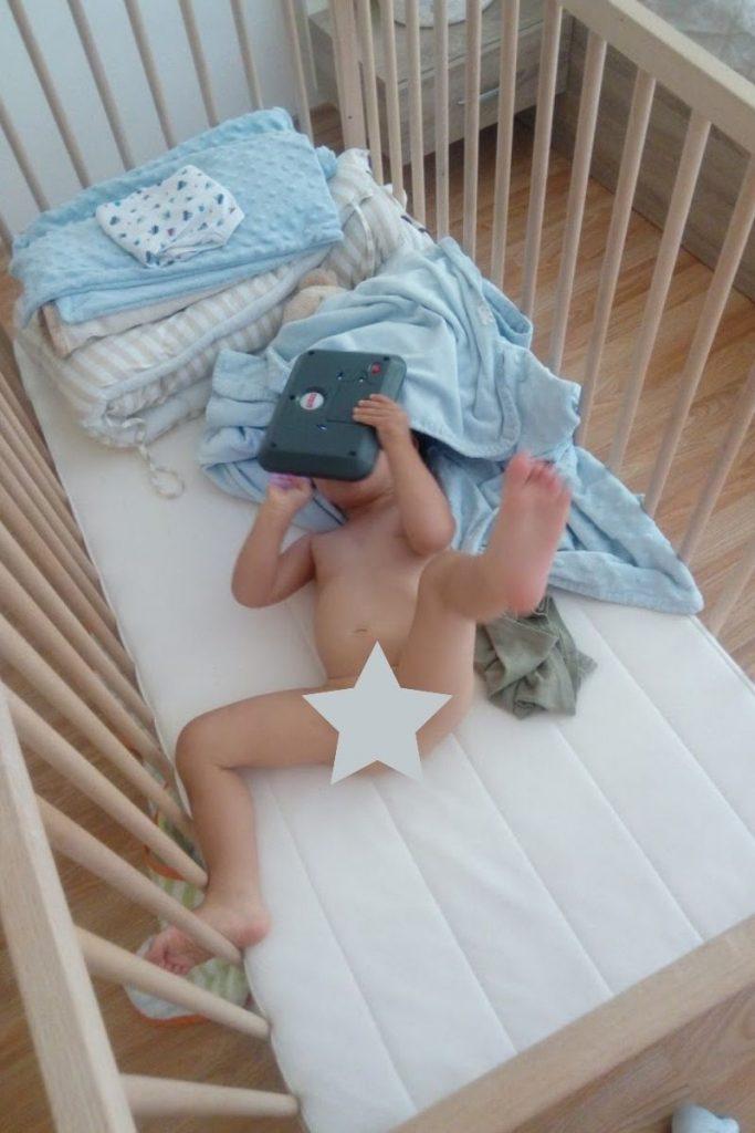 baby spielt im kinderbett nackt, will nicht gewickelt werden